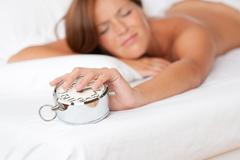 white lounge - woman holding alarm clock - stock photo