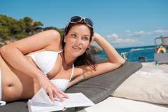 Stock Photo of attractive woman sunbathing on luxury boat
