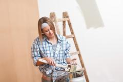 Home improvement: smiling woman with paint and brush painting wall Stock Photos