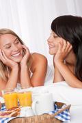 two happy women having breakfast - stock photo