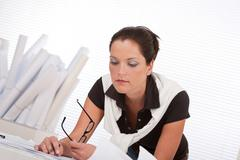 young female architect with plans - stock photo