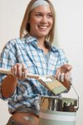 home improvement: smiling woman holding can and brush - stock photo