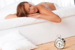 white lounge - young woman sleeping on white bed - stock photo