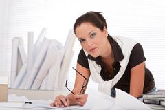 Young female architect with plans at the office Stock Photos