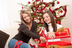 two women packing christmas present - stock photo