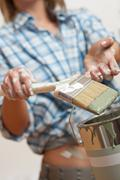 Home improvement: woman holding paint brush Stock Photos