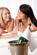 two women toasting with champagne in bedroom - stock photo