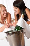 Two smiling women drinking champagne in luxury hotel room Stock Photos