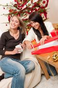 Two young woman wrapping christmas present Stock Photos