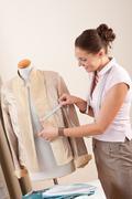 female fashion designer taking measurement - stock photo