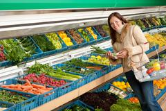 Grocery store shopping - woman holding spring onion Stock Photos
