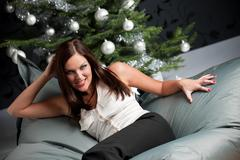 Provocative sexy woman posing in front of christmas tree Stock Photos