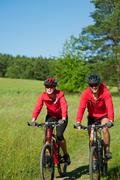 young couple with mountine bike in spring nature - stock photo