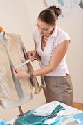 Female fashion designer taking measurement Stock Photos