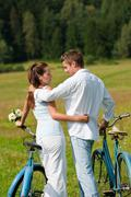 Romantic young couple with old bike in spring nature Stock Photos