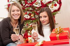 two young woman with champagne and christmas tree - stock photo