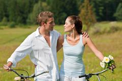 romantic young couple with old bike in spring nature - stock photo