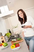 young woman with glass of red wine in the kitchen - stock photo