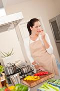 happy woman biting red pepper in the kitchen - stock photo