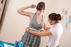 female fashion designer measuring model for fitting - stock photo