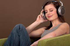 student series - young brown hair woman listening to music - stock photo