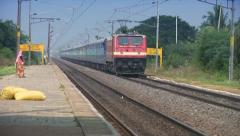 Indian passenger train passes by a countryside. Stock Footage