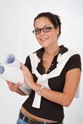 Stock Photo of smiling female architect with glasses holding plans