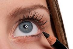 Blue eye, woman applying black make-up pencil Stock Photos
