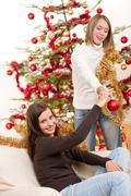 two smiling women with christmas decoration - stock photo