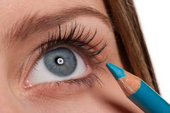 blue eye, woman applying turqouise make-up pencil - stock photo