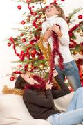 Two young woman having fun with christmas decoration Stock Photos