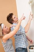 Home improvement: man painting wall with paintbrush Stock Photos