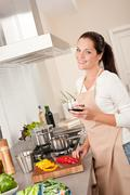woman with glass of red wine in the kitchen - stock photo