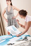 model fitting by female fashion designer - stock photo