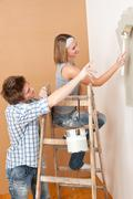 home improvement: young couple painting wall - stock photo