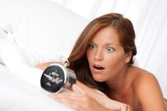 white lounge - shocked woman with alarm clock - stock photo