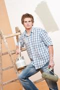 Home improvement: young man with paint roller Stock Photos