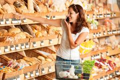 Grocery store: young woman holding mobile phone Stock Photos