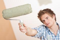 home improvement: young man holding paint roller - stock photo