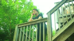 Calling summer cell phone talking talk outside communicate outdoors deck Stock Footage