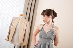 fashion model trying gray dress in designer studio - stock photo
