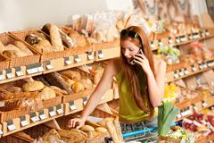 grocery store: red hair woman with mobile phone - stock photo