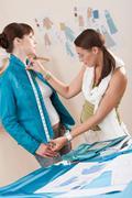 female fashion designer measuring jacket on model - stock photo