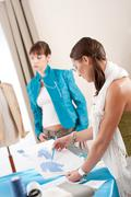 fashion model trying turquoise jacket in designer studio - stock photo