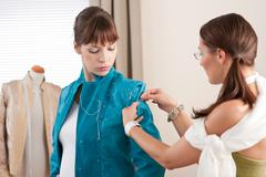 model fitting by female fashion designer - stock photo