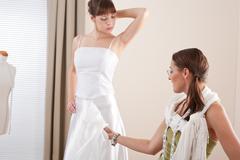 Stock Photo of fashion model fitting white wedding dress by designer
