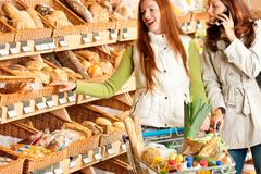 Grocery store: red hair woman and brunette in winter outfit Stock Photos