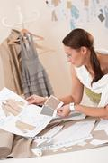 female fashion designer working with sketches - stock photo