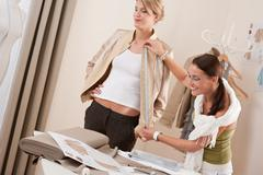 Stock Photo of fashion model fitting clothes by professional designer