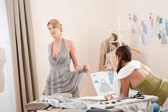 fashion model fitting dress by professional designer - stock photo